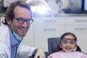 Portrait of smiling dentist and young patient in dental clinic
