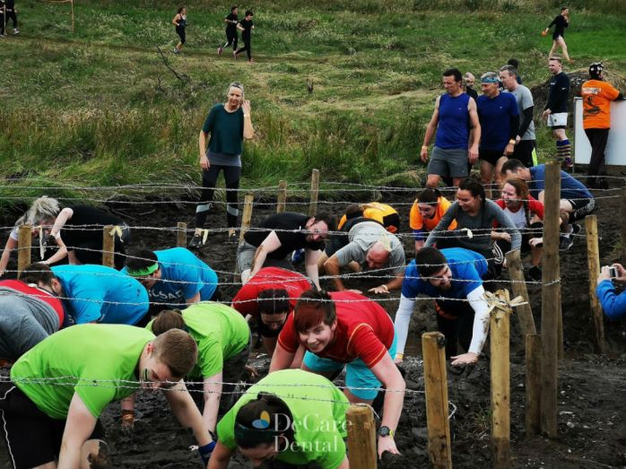 Some Tough Mudder participants taking part in the 'Kiss of Mud' obstacle.